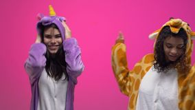 Women in funny animals jumpsuits dancing and having fun on pajamas party slow mo. Stock footage stock video footage