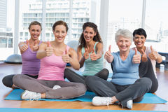 Women gesturing thumbs up in yoga class Royalty Free Stock Photography