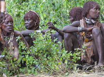 Women get ready for dancing at bull jumping ceremony. Turmi, Omo Valley, Ethiopia Stock Photography