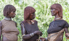 Women get ready for dancing at bull jumping ceremony. Turmi, Omo Valley, Ethiopia. Stock Images