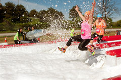 Women Get Sprayed With Bubbles Jumping Into Foam Pit Royalty Free Stock Photography