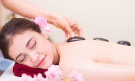 Women is getting Hot stone treatment Spa. Women is getting Hot stone treatment in Spa Stock Photo