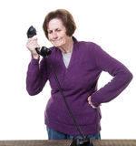 Women getting sales call. A fed up older woman getting another sales or political call stock image