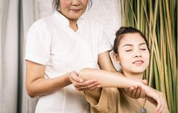 Women is getting Thai massage stretching position on arm Stock Image