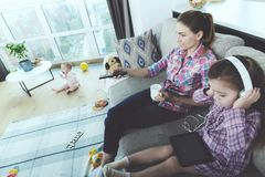 AThe woman and the girl are sitting on the couch and do not follow the baby. The baby sits on the floor. The women and the girl are sitting on the couch and do Royalty Free Stock Photography