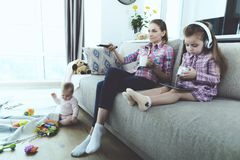 AThe woman and the girl are sitting on the couch and do not follow the baby. The baby sits on the floor. The women and the girl are sitting on the couch and do Royalty Free Stock Images
