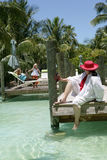 Women and girl on vacation. Two women and a young girl along a dock with palm trees near the water, caucasian/white Royalty Free Stock Photos