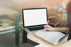Women or girl writing down on blank note book or making memo on. Empty memorandum or diary book with blank screen laptop (notebook) girl or women writing down stock photography