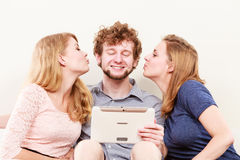 Women girls kissing man guy with tablet. Fun. Young women girls kissing handsome men guy with tablet. Happy friends having fun relaxing at home royalty free stock image