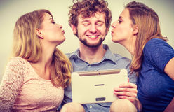 Women girls kissing man guy with tablet. Fun. Royalty Free Stock Photos