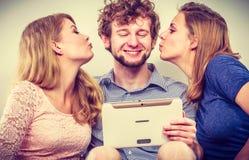 Women girls kissing man guy with tablet. Fun. Royalty Free Stock Photos