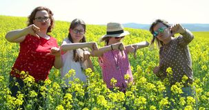 Women and girls showing thump down on a oilseed rape field - disappointment. stock footage