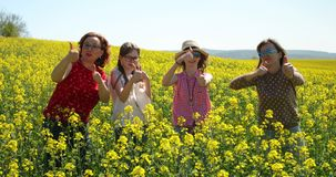 Women and girls showing thump up on a oilseed rape field - success. stock footage
