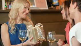 Women giving present to friend at wine bar stock video footage