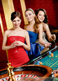 Women with glasses of spirits play roulette. Women keeping glasses of spirits play roulette at the gambling house Royalty Free Stock Photography