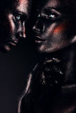 Women in glitter and black paint faceart. In studio Royalty Free Stock Images
