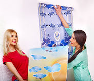 Women glues wallpaper at home. Stock Photo