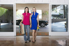 Women Going On Shopping Trip. Full length portrait of two beautiful women with bags on shopping trip Royalty Free Stock Image