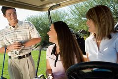 Women In Golf Cart Looking At Man Royalty Free Stock Images