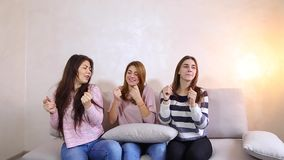 Girls listen to music and dance, smiles on their faces and sitting on sofa background of light wall in room. Women in good spirits listen to music and dance stock video footage