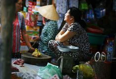 Women gossiping in a market. Woman sat by their stalls gossiping at a market along the Mekong Delta, Asia Royalty Free Stock Photo