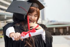 Women with graduation suit, Commencement day. Smile Asian beautiful young female students with black graduation gowns hug each other with modern bangkok city Stock Photography