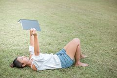 Women is on the grass and beautiful. she hold book. she wear white dress royalty free stock image
