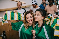 Women in green fan t-shirts holding fan scarf and their male friends standing behind during watch of soccer match. At bar royalty free stock photos