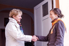 Women greeting girl. Senior women greeting young girl in the doorway Royalty Free Stock Photo
