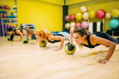 Women group with balls doing push up exercise. Fitness workout. Female sport teamwork in gym. Fit class, aerobic Stock Images