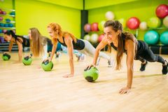 Women group with balls doing push up exercise. Fitness workout. Female sport teamwork in gym. Fit class, aerobic royalty free stock photography