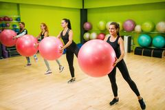 Women group with big balls doing exercise, fitness. Workout. Female sport teamwork in gym. Fit class, aerobic Stock Photos