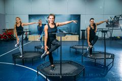 Women group doing fit exercise on sport trampoline. Fitness workout. Female teamwork in gym. Aerobic class royalty free stock images