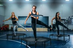 Women group on sport trampoline, fitness workout. Female teamwork in gym. Aerobic class Stock Image
