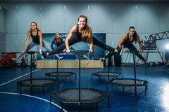 Women group on sport trampoline, fitness workout. Female teamwork in gym. Aerobic class royalty free stock photos