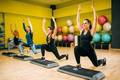 Women group on step aerobic training. Female sport teamwork in gym. Fit class, fitness exercise in motion Stock Photo