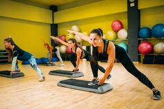 Women group on step aerobic training. Female sport teamwork in gym. Fit class, fitness exercise in motion Stock Photography