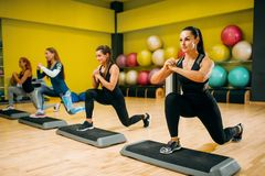 Women group on step aerobic workout. Female sport teamwork in gym. Fit class, fitness exercise in motion Stock Photography