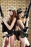 Women with guns. Two sexy women in military uniform posing against brick background Royalty Free Stock Photos