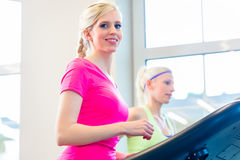 Women in gym doing sport on treadmill Royalty Free Stock Images
