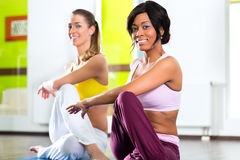 Women in the gym doing yoga exercise for fitness. Young women doing yoga and meditation in gym for better fitness, caucasian and latina people Royalty Free Stock Images