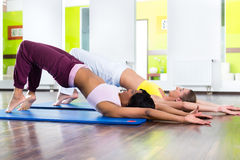 Women in the gym doing yoga exercise for fitness. Young women doing yoga and meditation in gym for better fitness, caucasian and latina people Royalty Free Stock Photo