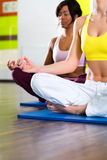 Women in the gym doing yoga exercise for fitness. Young women doing yoga and meditation in gym for better fitness, caucasian and latina people Stock Image
