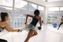 Women at gym during resistance band workout. Strong women using a resistance band in her exercise routine at fitness studio. Personal trainer and women at gym Royalty Free Stock Images