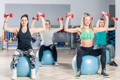 Women on gymnastic balls doing exercises with dumbbells. In the gym with a coach Stock Images