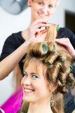 Women at the hairdresser being curled Stock Photo
