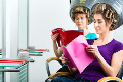 Women at the hairdresser with hair dryer Stock Photos