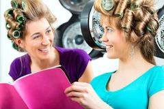 Women at the hairdresser with hair dryer Royalty Free Stock Photography
