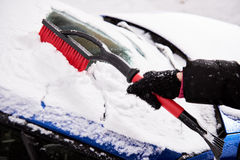 Women hand in black glove removes snow from car windshield in winter day Stock Images