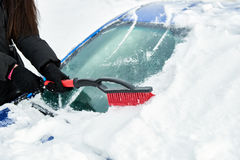 Women hand in black glove removes snow from car windshield in winter day Stock Photo